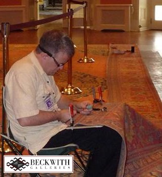 A man holding tools, sitting on a chair and restoring a large carpet in his lap