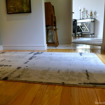 Photo of a grey carpet on wood flooring in front of an doorway