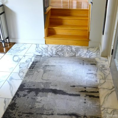 Photo of a grey carpet on marble flooring in front of an entryway