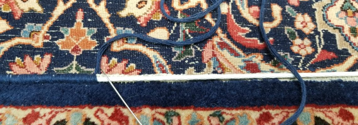 Photo of a multi-coloured rug with a blue yarn threaded needle on top in the process of being mended