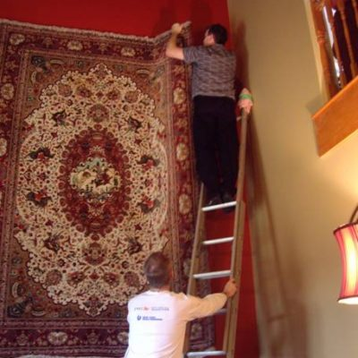 A man on a ladder velcro hanging a rug while another man holds the base of the ladder steady
